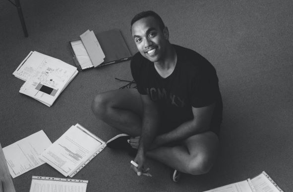 35 year-old Larrakia man Jonathan sitting cross-legged on carpeted floor surrounded by study/work papers