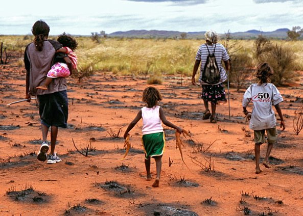 Two Aboriginal women & 3 Aboriginal children walking on Country away from the camera