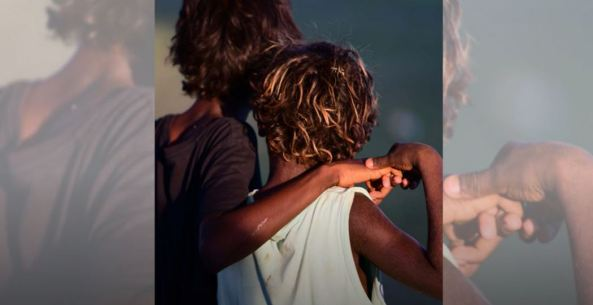 view from waist up of two Aboriginal children one with arm around the shoulders of the other facing away from the canera