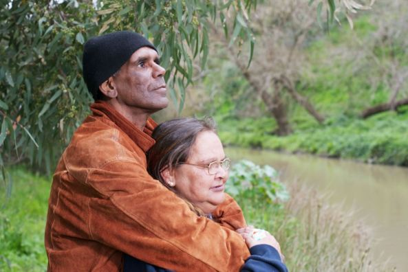 Aboriginal man with arms around Aboriginal woman looking out across river in Australian landscape