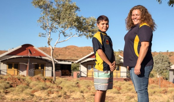 Aboriginal woman and male youth in foreground against building in remote Australia