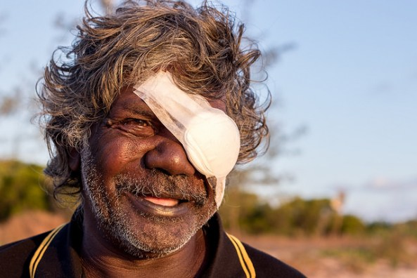 Aboriginal man with eye bandage set against rural landscape