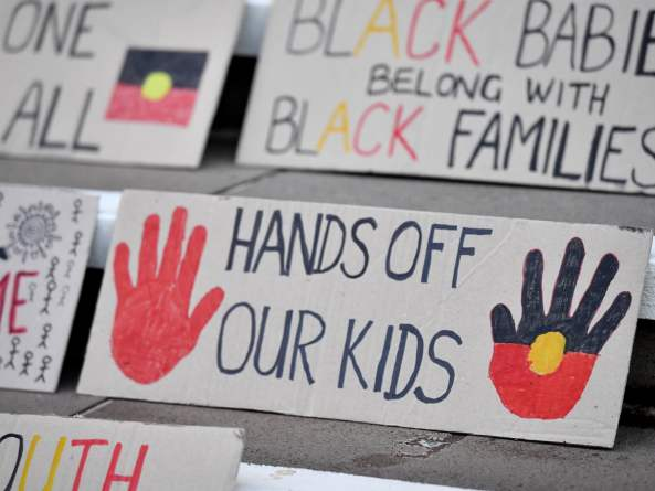 placards against steps with Hands off our kids, black babies belong with black families