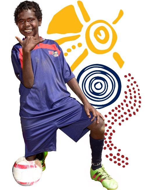 Aboriginal boy in football uniform kneeling on soccer ball