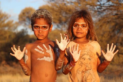 Young Aboriginal children Quinton and Jasalia Williams with face, hair, hands & chest paint, cultural day on country
