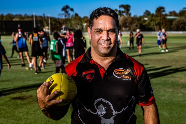 Aboriginal man with Right Tracks Program shirt holding football, standing on football field