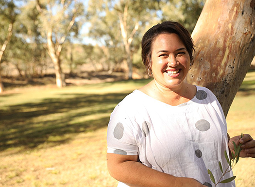 Katherine Liddle standing in front of a tree in bushland holding a twig with leaves, smiling