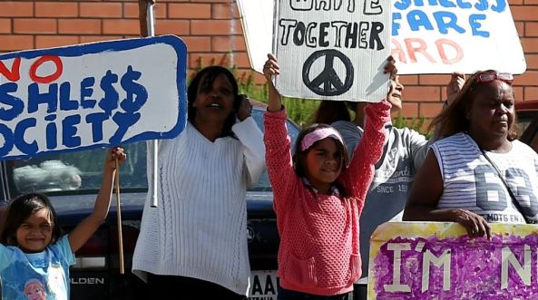 3 Aboriginal woman & two Aboriginal children holding No Cashless Debit Card placards