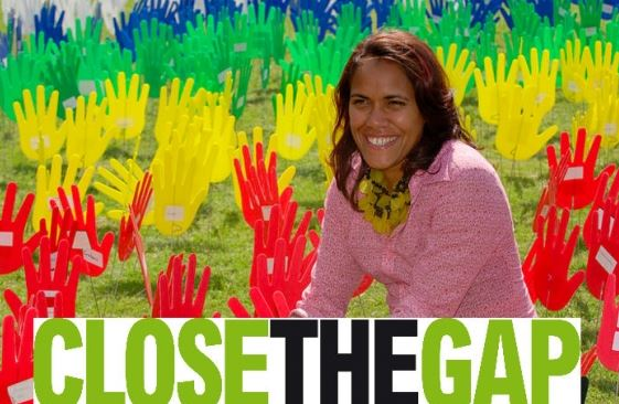 Kathy Freeman sitting on lawn with yellow green red blue cut out hands on sticks with text 'Close the Gap'