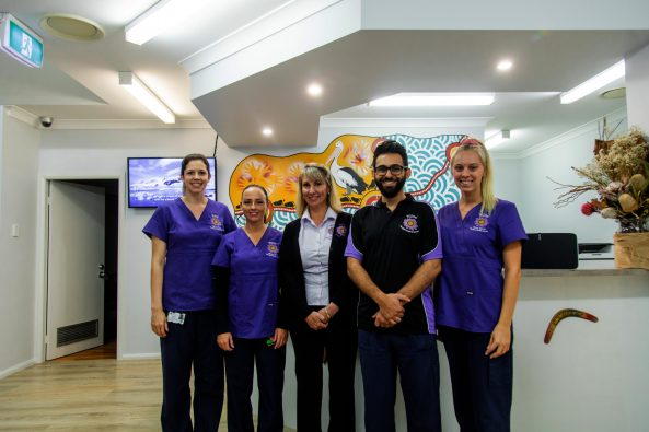 5 staff in purple uniforms standing at front of reception desk at Gulgul Yirra Dental Clinic in Wyong