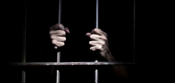 Aboriginal person's hands gripping bars of jail cell