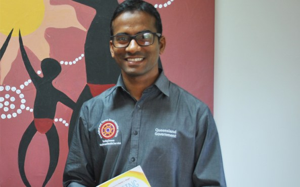Clinical Psychologist Arvind Ponnapalli, Cherbourg Qld, in CRAICCHS logo business shirt standing against Aboriginal art