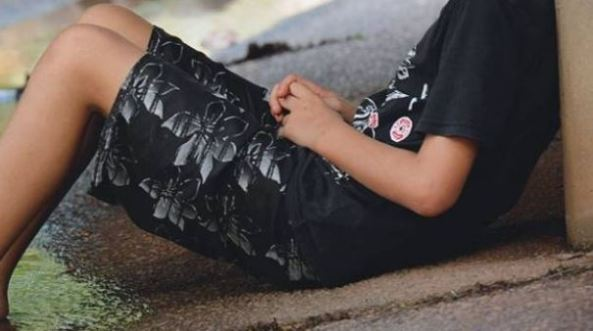 torso of Aboriginal youth sitting on pavement leaning against a wall