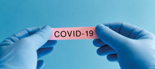 gloved hands holding pink piece of paper with text 'COVID-19'