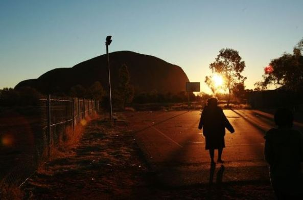 silhouette of Aboriginal woman walking towards Uluru as sun is setting