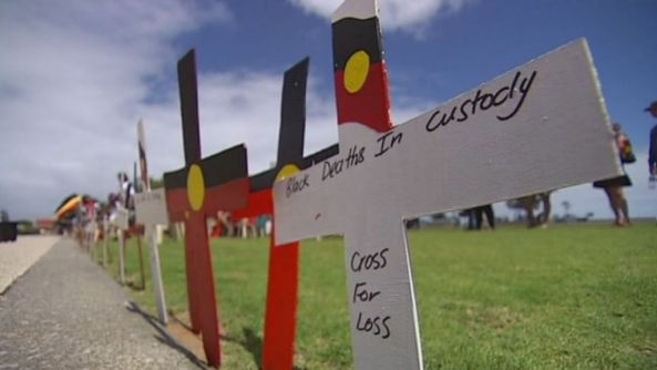 crosses in row on grass with Aboriginal flag painted on them & words Black Deaths In Custody Cross For Loss