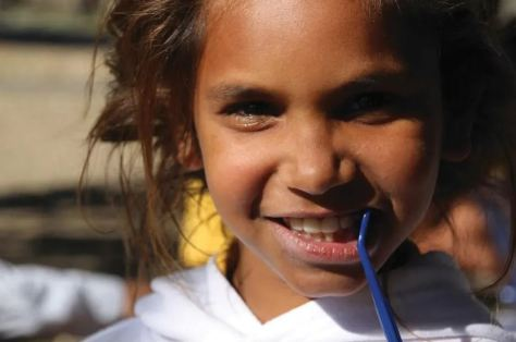Aboriginal girl holding blue toothbrush to her mouth