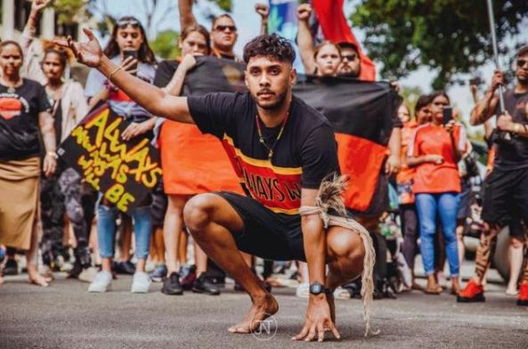 Derek Nanup, 23, WA Young Person of the Year, doing Aboriginal dance with Always was Always will be march members in background