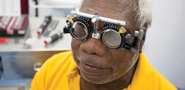 Aboriginal man wearing eye test equipment spectacles