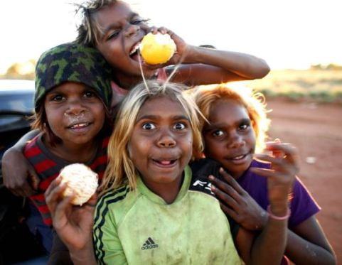 4 Aboriginal kids from NPY Lands arms around each other smiling & making funny faces for the camera, holding oranges, car & outback in the background