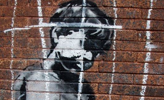 spray painted image of an Aboriginal child on a brick wall overlaid with white chalk lines representing jail bars