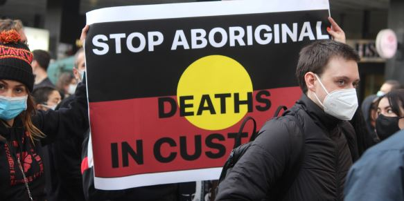 protest march female & male wearing covid-19 maskes with banner in background of Aboriginal flay overlaid with words 'stop Aboriginal Deaths in Custody'