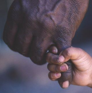 Aboriginal adult hand with small Aboriginal child's hand holding one of the fingers