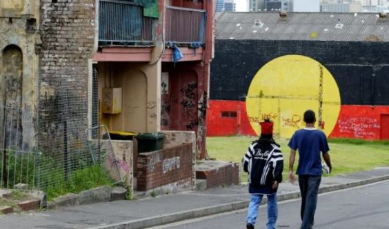 rear view of two Aboriginal youth walking down a road in Redfern, derelict terrace houses & entire wall painted with Aboriginal flag & graffiti