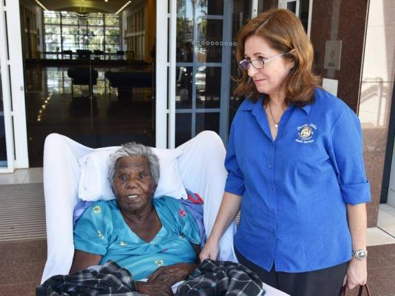 Aboriginal Elder Mildred Numamurdirdi sitting in an armchair with pillow behind head, lap rug & Danila Dilba staffer standing by her side