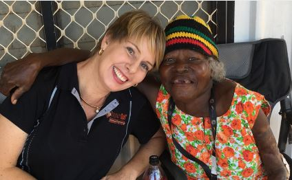 Aboriginal Elder sitting in a wheelchair with sleeveless orange floral dress & black yellow green stripe beanie with her arm around a health care worker