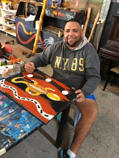 Aboriginal man painting at The Glen