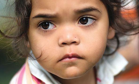 close up of face of young Aboriginal girl looking sad