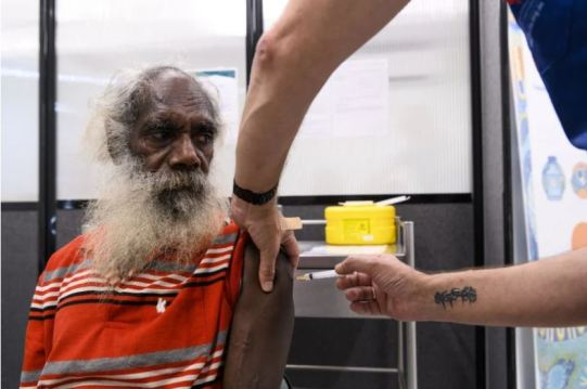 Binjari man Christopher Frith, 62 (red black white grey polo shirt, long grey beard & hair on balding head) get's covid-19 vaccine at Katherine's Wurli Wurlinjang Health Service, looks worriedly to the side as the vaccine is injected