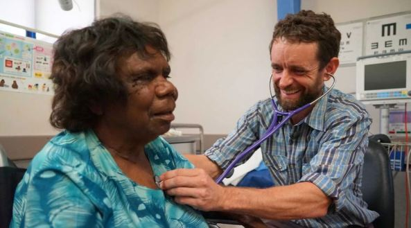 Dr Simon Quilty with stethoscope to Aboriginal woman's chest