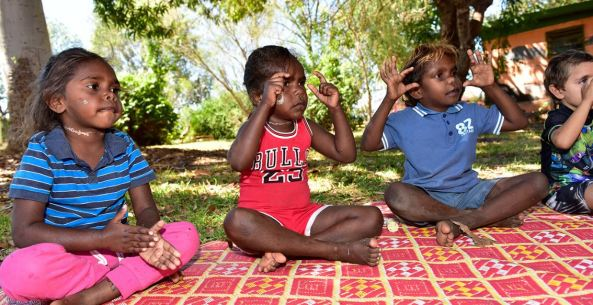4 young Aboriginal children, 1 girl, 3 boys sitting outside on outdoor rug all looking in one direction making hand signals presumably to a song