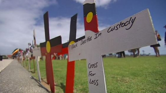row of crosses along edge of path, painted with the Aboriginal flag & one with the words 'Black Deaths in Custody - Cross for Loss'