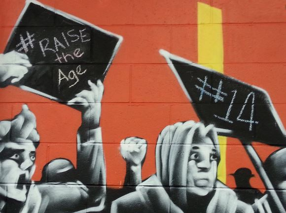 graffeti orange painted brick wall & black & white people holding signs #raise the age and #14
