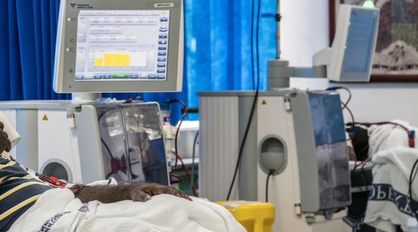 from torso down Aboriginal man receiving dialysis, background is monitor & dialysis machine, blue hospital curtain