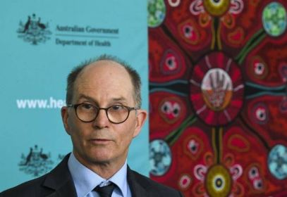 portrait of Professor Paul Kelly, Australian Government Chief Medical Officer against Australian Government Department of Health banner with Aboriginal dot art painting