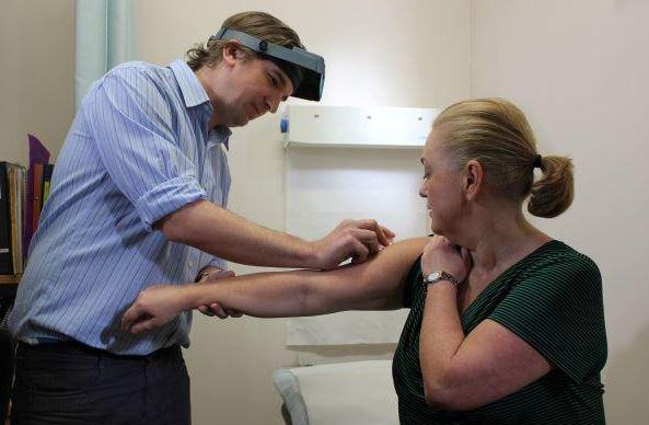 GP swabbing arm of patient in consult room