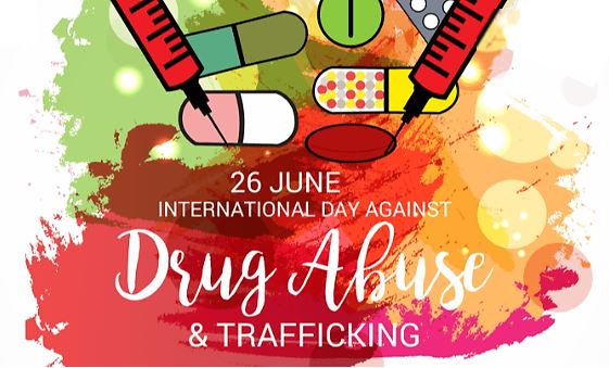 banner background blocks of green, red, yellow overlapping watercolour paints, top 2 syringes pointing down 2 capsules, 2 tablets & pack of tablets, text '26 June International Day Against Drug Abuse & Trafficking' in white font