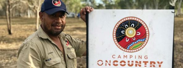 Aboriginal man wearing navy cap with Camping on Country logo & khaki shirt in bush setting with hand on Camping on Country sign