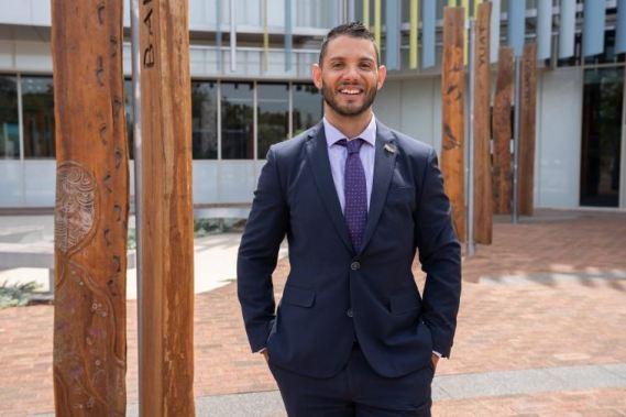 Professor Braden Hill in navy suit, purple shirt & tie standing outside university building with wooden totem poles