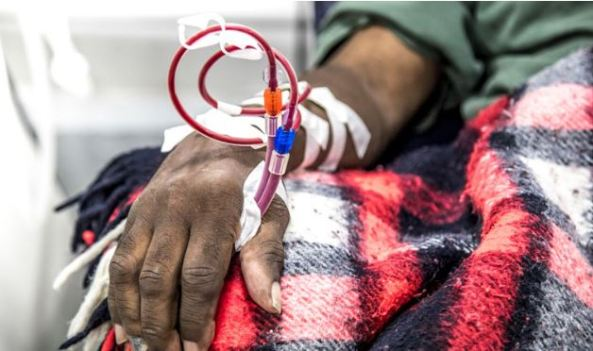 arm of Aboriginal man linked to dialysis with red black white tartan blanket over lap