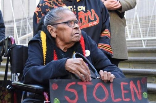 Eunice Wright in wheel chair holding sign with 'stolen' written on it at rally in Melbourne