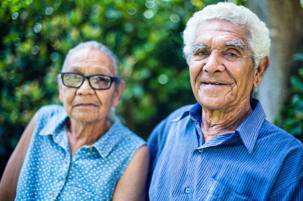 elderly Aboriginal man and woman against blurred green foliage