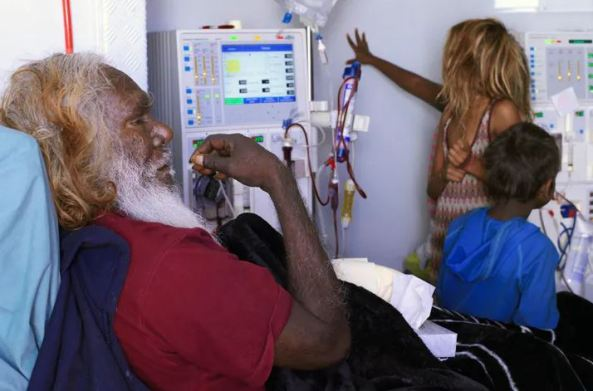 older Aboriginal man in hospital bed with young Aboriginal girl looking at machines & young Aboriginal boy sitting on his bed