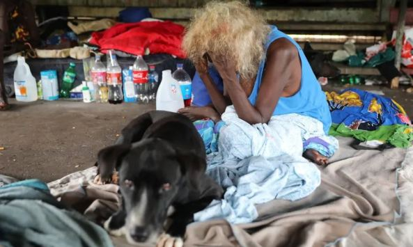 older Aboriginal woman sitting cross-legged with face in hands, makeshift bedding, surrounded by rubbish, black dog looking at camera