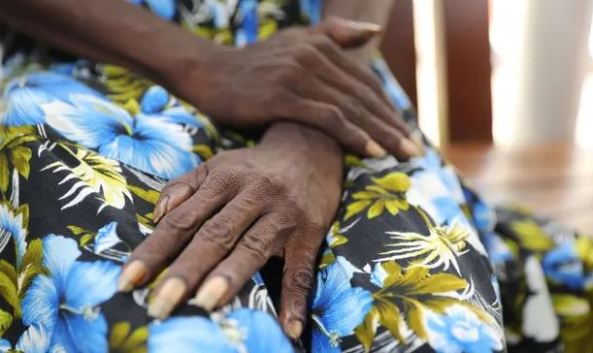 photo of Aboriginal woman's hands in her lap, green blue hibiscus dress