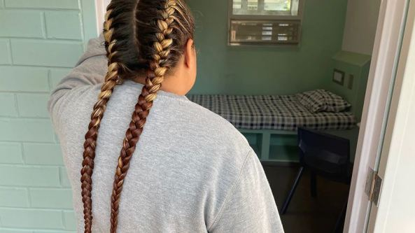photo of back of woman with two long plaits at the door of a jail cell